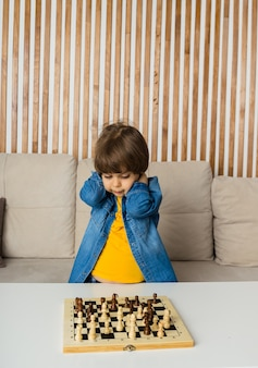 Bouleversé petit garçon est assis dans une pièce et joue aux échecs