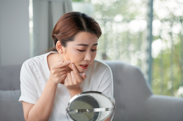 Bouleversé a souligné l'acné triste femme avec la peau à problèmes serre le bouton à la maison à l'aide d'un petit miroir rond