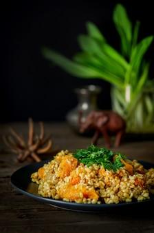 Boulgour à la citrouille sur une table en bois. recettes végétariennes de la cuisine indienne.