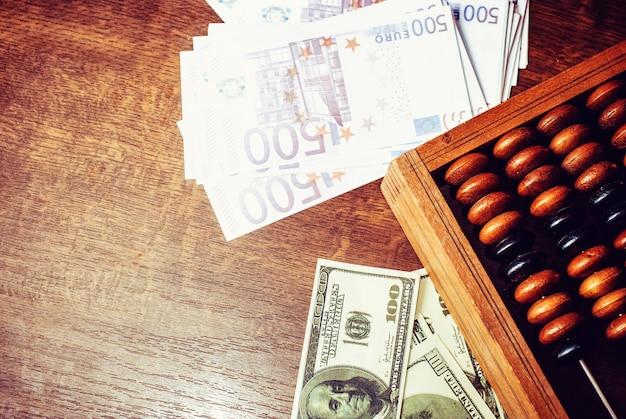 Boulier antique avec dollar américain et euro sur fond de table en bois ancien