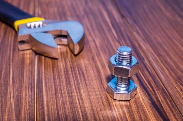 Boulon et écrou en métal sur fond de bois vintage marron avec clé à molette