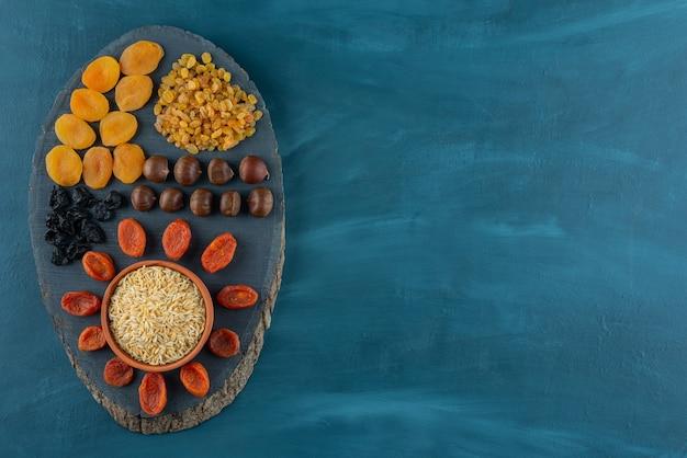 Bouquet d'abricots secs, de prunes et de raisins secs sur un morceau de bois.