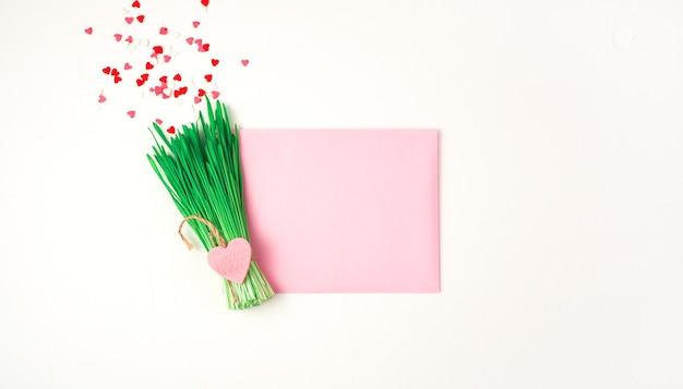 Bouquet abstrait d'herbe et de petits coeurs et une enveloppe rose sur fond clair.