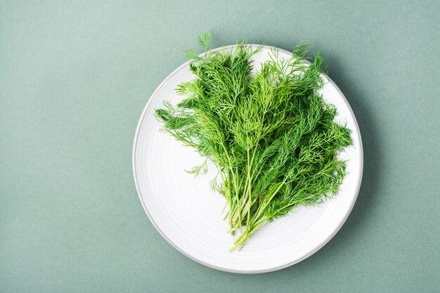 Un bouquet d'aneth frais sur une assiette sur fond vert. verts vitaminés dans une alimentation saine. vue de dessus