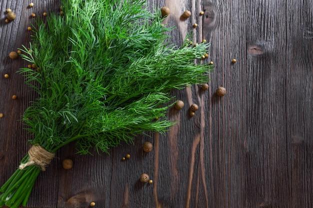 Bouquet d'aneth frais et d'épices sur une table en bois sombre.