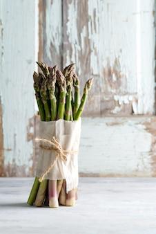Bouquet d'asperges vertes biologiques fraîchement cueillies sur fond de pierre claire.
