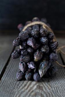 Bouquet d'asperges violettes fraîches sur un fond en bois.