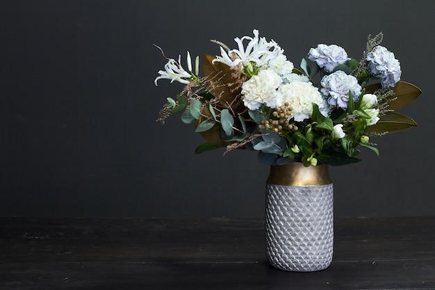 Bouquet aux tons blancs dans un style vintage dans un vase en céramique sur fond sombre