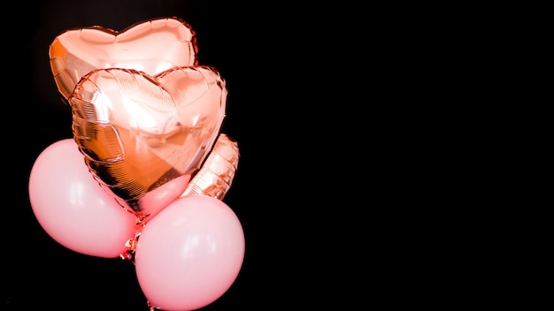 Bouquet de ballons en aluminium en forme de coeur de couleur rose isolés sur fond noir. amour. célébration de vacances. fête de la saint-valentin. élément de décorations pour fête d'anniversaire, mariage ou festival.