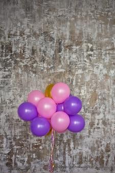 Bouquet de ballons lumineux contre un mur texturé. copier l'espace