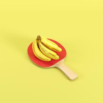 Bouquet de bananes mûres jaunes sur une raquette de ping-pong isolée sur fond jaune
