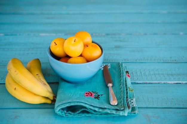 Bouquet de bananes près de prunes fraîches dans un bol