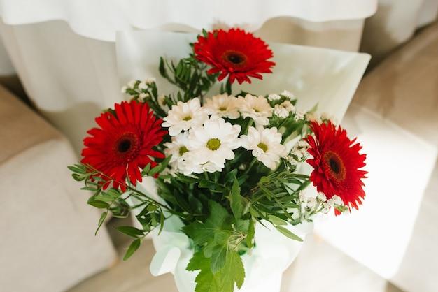 Un bouquet de beaux gerberas rouges et de chrysanthèmes blancs dans un vase