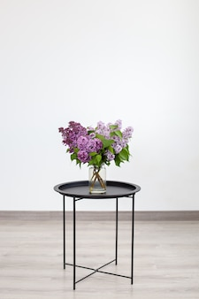 Bouquet de belles fleurs lilas de printemps dans un vase sur une table basse vintage noire, décoration intérieure. design d'intérieur.