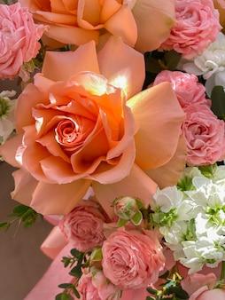 Un bouquet de belles fleurs de pêcher dans une boîte se dresse sur une chaise dans un fleuriste. une composition de roses, de mattiola blanche et de chrysanthème. un cadeau doux pour des vacances