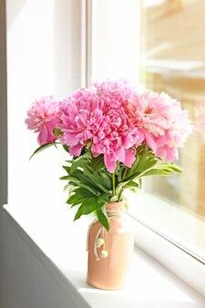 Bouquet de belles fleurs de pivoine sur le rebord de la fenêtre