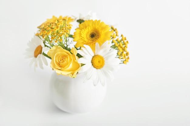 Bouquet de belles marguerites dans un vase blanc