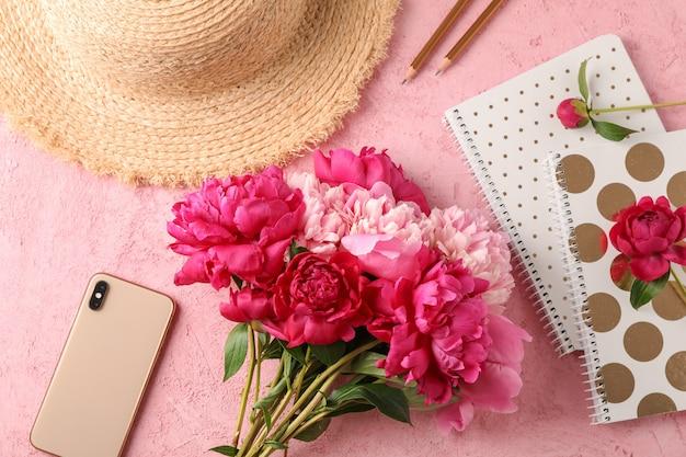 Bouquet de belles pivoines, chapeau de paille, téléphone, cahiers et crayons sur fond de couleur