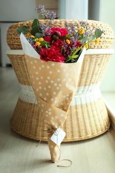 Bouquet avec de belles pivoines près de l'ottoman dans une pièce lumineuse