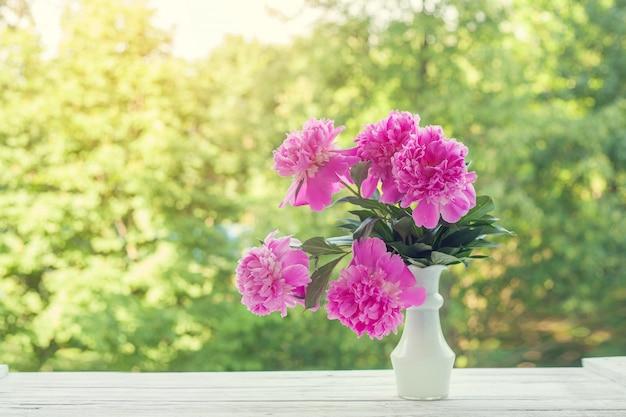 Bouquet de belles pivoines rose pâle dans un vase blanc sur fond de nature vert.