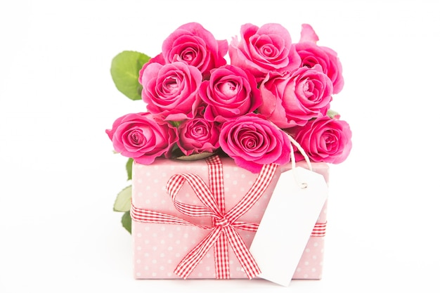 Bouquet de belles roses roses à côté d'un cadeau rose avec une carte vide sur fond blanc