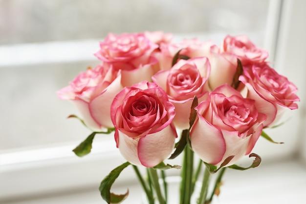 Bouquet de belles roses roses sur la fenêtre. carte de saint valentin. espace pour le texte. composition florale. modèle de carte de voeux pour la fête des mères et le 8 mars.