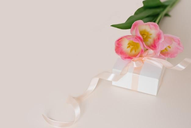 Un bouquet de belles tulipes et un cadeau sur une vue de dessus de fond beige. fond de fête des mères, saint-valentin, journée internationale de la femme. vacances, offrez un cadeau.