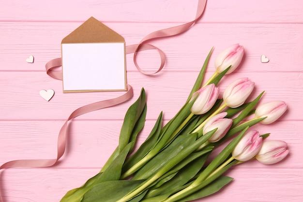 Un bouquet de belles tulipes et un cadeau sur une vue de dessus de fond en bois