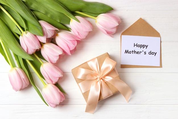 Un bouquet de belles tulipes et une carte pour le texte sur un fond en bois