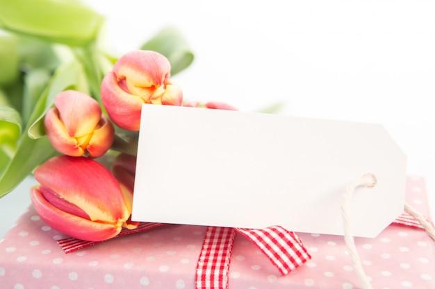 Bouquet de belles tulipes à côté d'un cadeau avec une carte vide
