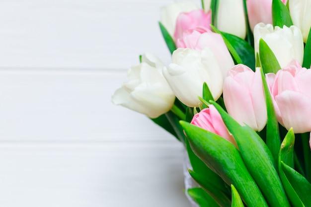 Bouquet de belles tulipes roses sur mur blanc