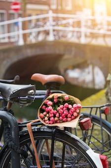 Un bouquet de belles tulipes roses se trouve sur le coffre du vélo. amsterdam