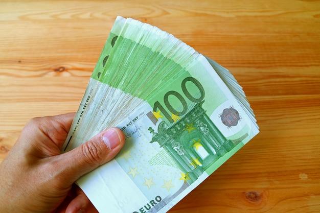 Bouquet de billets de 100 euros en main d'homme avec une table en bois en toile de fond