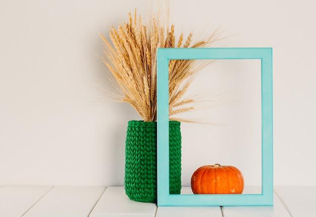 Un bouquet de blé sec et de seigle dans un vase tricoté vert