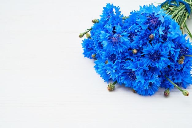 Bouquet de bleuets bleus sur bois blanc