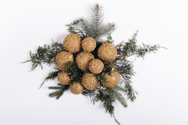 Bouquet de boules de noël dorées et de branches de sapin sur fond blanc