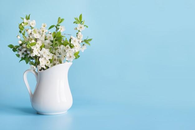 Bouquet de branche de cerisier en vase sur fond bleu.