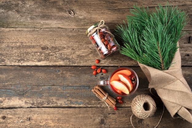 Bouquet de branches de pin, vin chaud et cannelle sur fond en bois.