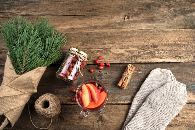 Bouquet de branches de pin, vin chaud et mitaines sur fond en bois.
