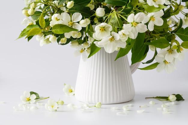 Bouquet de branches de pomme en fleurs sur une table brillante. fleurs blanches sur une branche