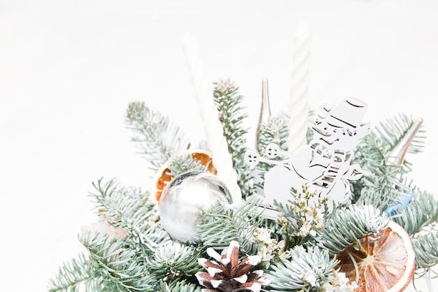 Un bouquet de branches de sapin renforcé d'un bonhomme de neige, des jouets de noël, des oranges séchées et des bougies blanches. bouquet de noël, lieu de copie, fond clair