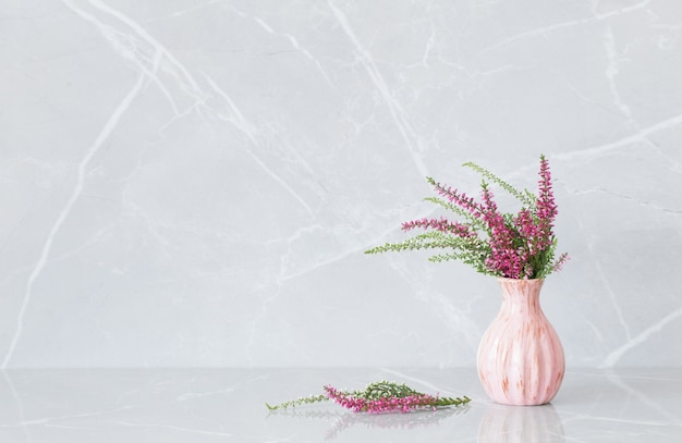 Bouquet de bruyère dans un vase sur fond de marbre gris