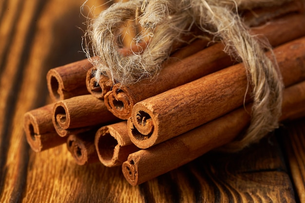 Un bouquet de cannelle attaché avec une corde sur bois