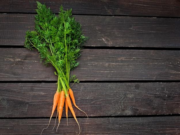 Bouquet de carottes fraîches avec des feuilles vertes sur fond en bois