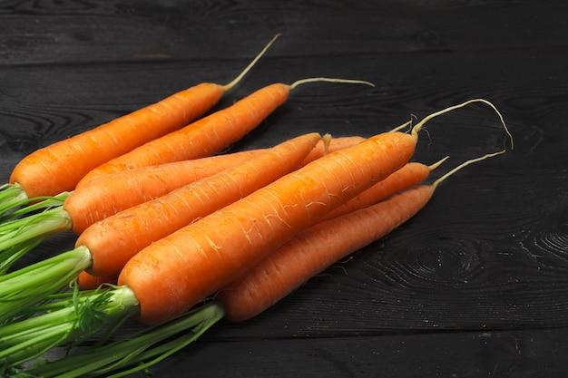 Bouquet de carottes fraîches avec des feuilles vertes sur une table en bois
