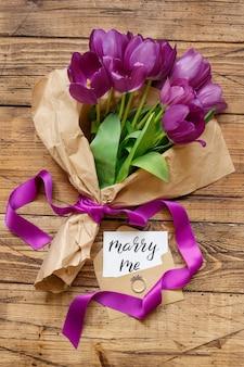 Bouquet et carte épouser moi sur la vue de dessus de table en bois