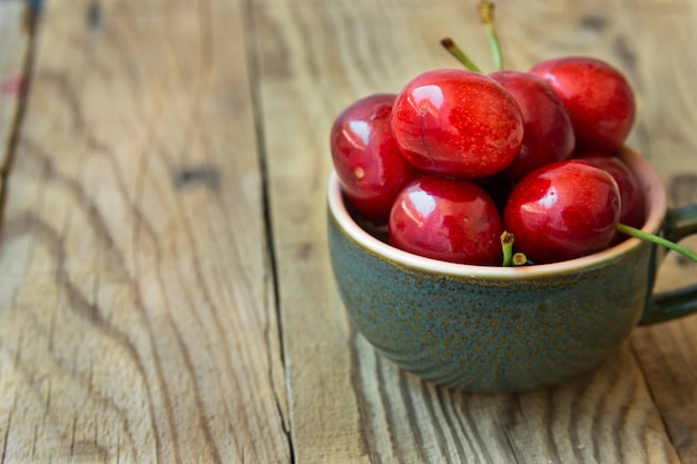 Bouquet de cerises douces brillantes colorées mûres dans une tasse de thé en céramique sur fond de bois