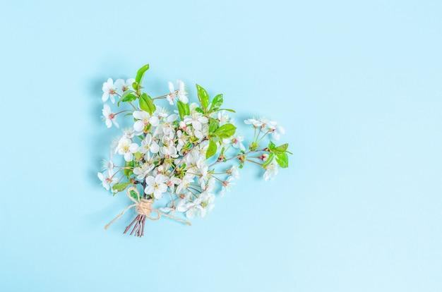 Un bouquet de cerises en fleurs sur une surface bleue