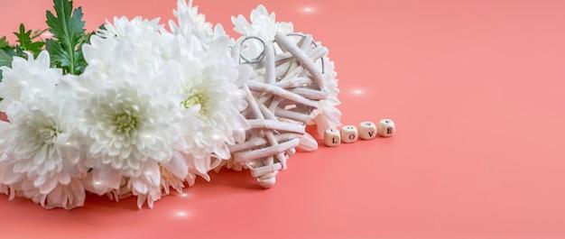 Bouquet de chrysanthèmes blancs, forme de coeur paille zéro déchet sur fond rose.