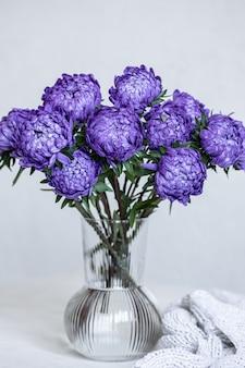 Un bouquet de chrysanthèmes bleus dans un vase en verre et un élément tricoté sur fond blanc, copiez l'espace.